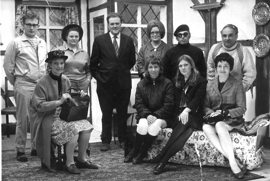 """The Cast & Set Standing, left to right: Brian Shaw (""""Michael""""), Patricia Rowley (""""Bella""""), Geoffrey Weaver (""""Fraser""""), Jacqueline Baskerville (""""Miss Laing""""), Clive West (""""Pierre""""), Sid West (""""Jeremy""""). Sitting, left to right: Margaret Lloyd (""""Mrs Trotter""""), Pat Quick (""""Jill""""), Ann Richards (""""Suzette""""), Dorothy Morris (""""Alison"""")."""