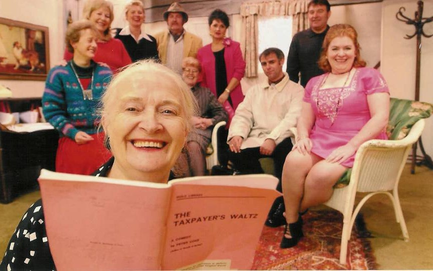"The cast (not very focused!) Background, left to right: Alison Shepherd (""Flora""), Doreen Davies (""Joyce""), Heather Cooper (""Oonagh""), David Spear (""Arthur""), Julie Greenwood (""Miss Timwell""), Lyn Brundle (""woman""), Tony Currell (""Barclay""), Barry Cooper (""Norman""), Denise Currell (""Maureen""). Foreground: Dorothy Morris (director/producer)"